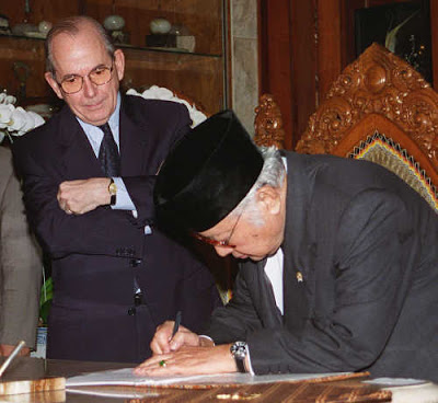 The Iconic Image of IMF Power: IMF Managing Director Michel Camdessus looking on as Indonesia's President Soeharto signs a second bailout agreement, January 1998